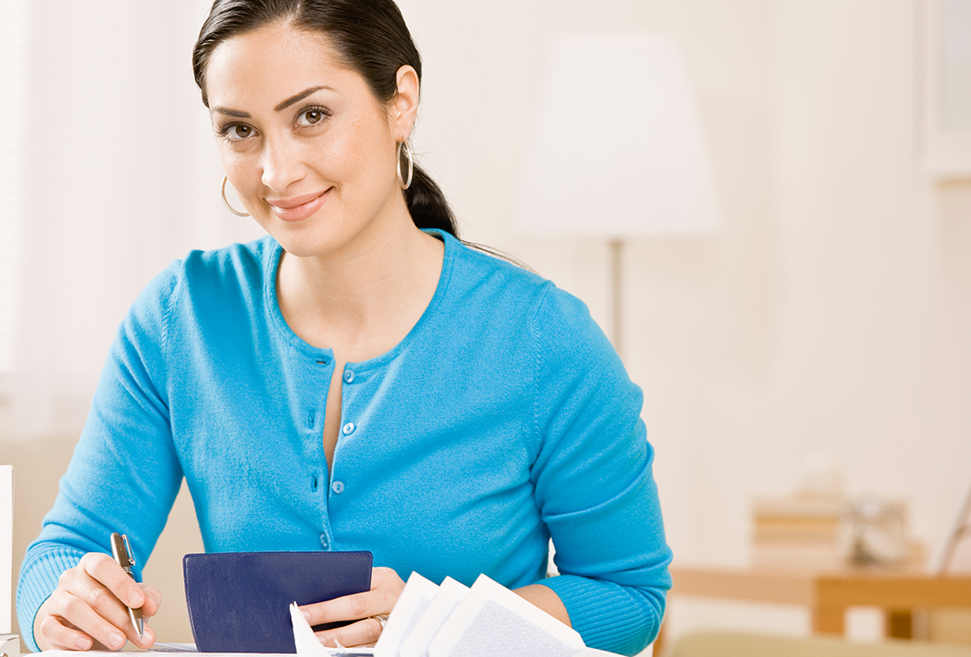Woman writing check from checkbook